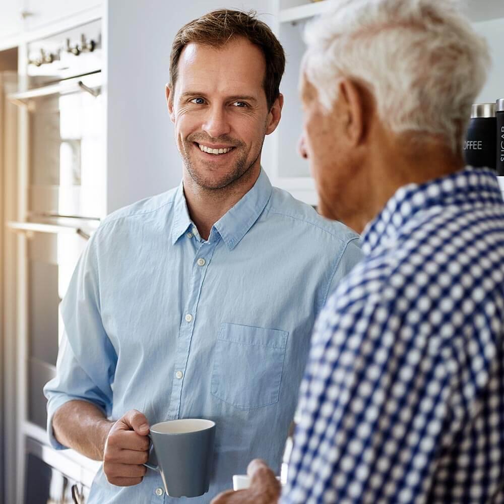 Young man talking to elderly man