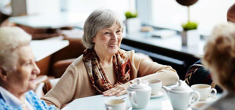 Four elderly people bonding over tea