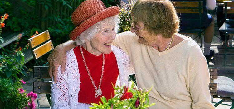 Two elderly women laughing and bonding