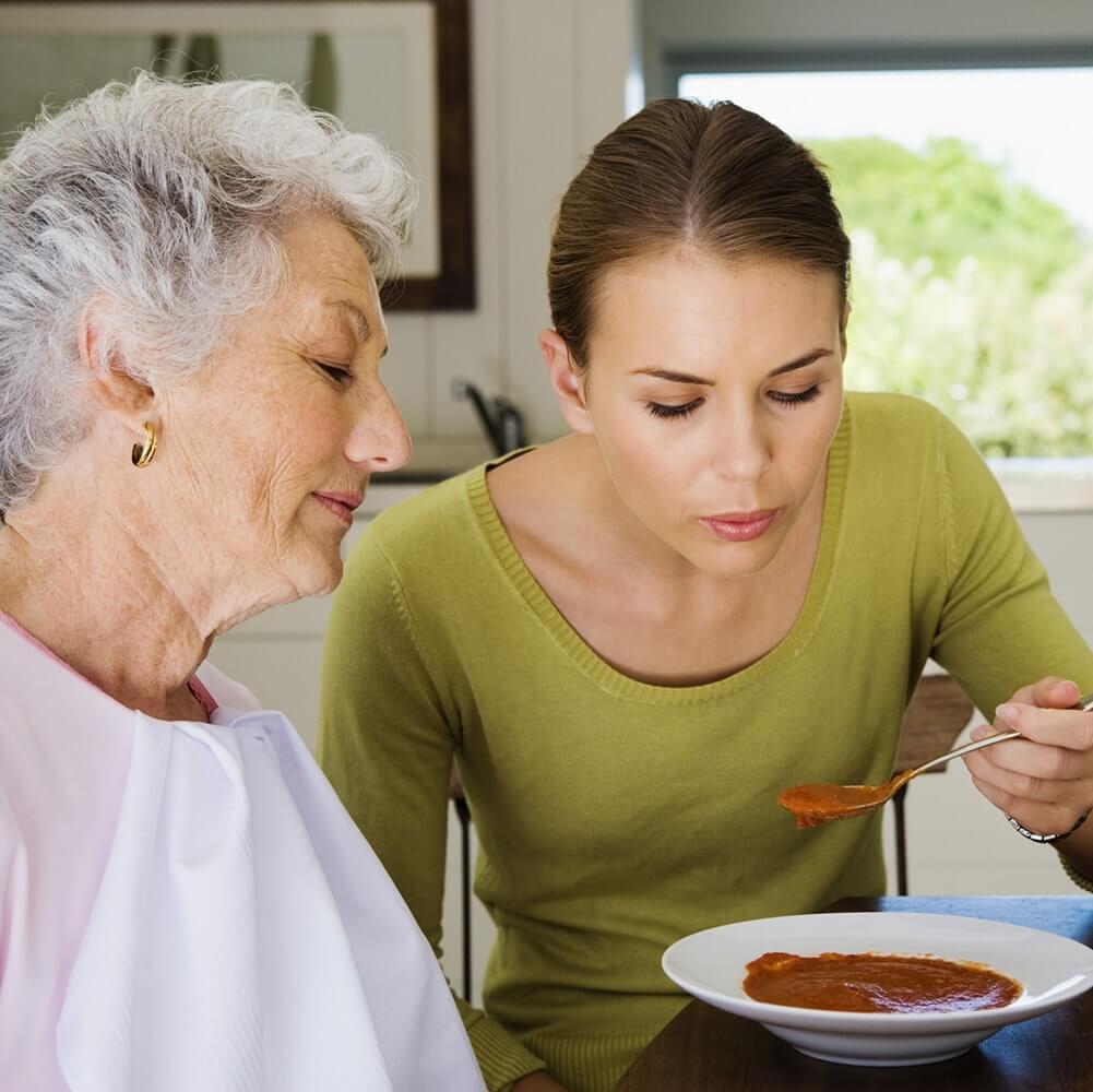 Woman feeding elderly woman soup