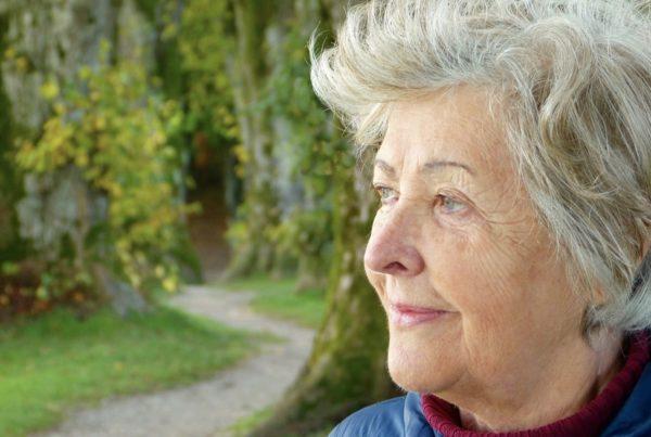 Elderly lady outside in a garden, smiling